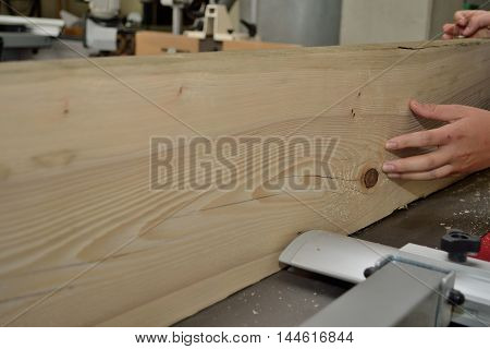 Wooden board is treated by a carpenter with a planer