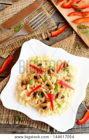 Pasta with fried mushrooms, red pepper and green onion. Pasta on a plate, fork and knife on old wooden background, chopped red pepper and green onions on a cutting board. Vegetarian recipe. Top view