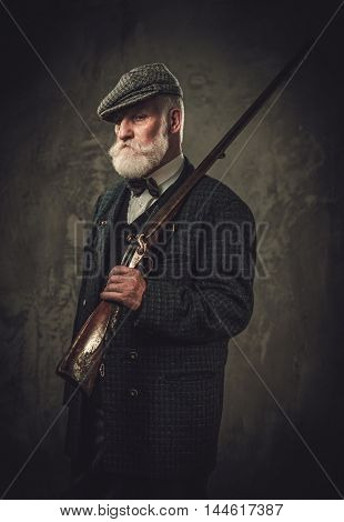 Senior hunter with a shotgun in a traditional shooting clothing on a dark background.