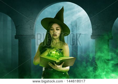 Asian Witch Woman Holding The  Book Of Magic
