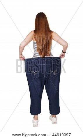 Young happy woman delighted with diet results, isolated on white. Girl celebrates weight loss success showing big size jeans on her slim figure. Good shape, healthy lifestyle and eating right concept.