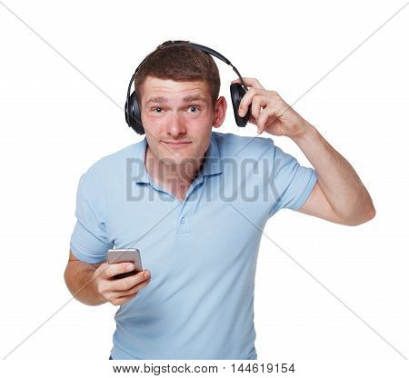 Happy young man with headphones opens one ear trying to hear someone through loud sound of music, isolated at white background. Guy listens music from his mobile smartphone with wireless earphones.