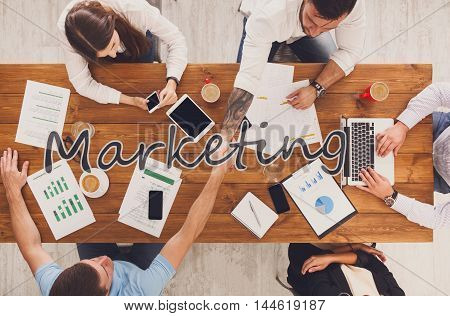 Marketing meeting. Business people work in office, top view of wood table with mobile phones, laptop, tablet and documents papers with diagram. Men and women team handshake, have contract conclusion.