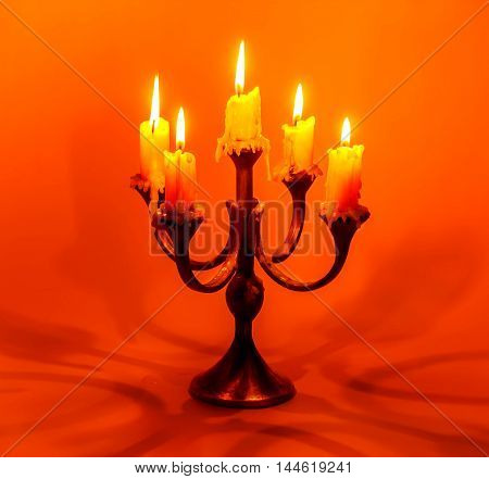 old candlestick with burning candles on a red background