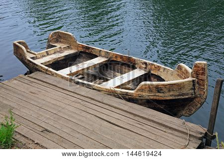 old wooden boat on the blue river
