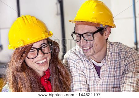 couple of engineers having fun consult the computer in a steel mill