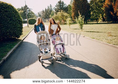 young mother walking with her baby and carries it in a beautiful pram