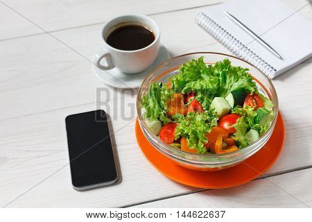 Healthy business lunch in office, vegetable salad bowl on white wooden desk. Organic meal, coffee, mobile phone and notepad with pen flat lay. Snack at break time