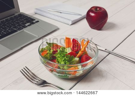 Healthy business lunch in office, vegetable salad bowl near laptop on white wooden desk and notepad with pen. Organic meal and red apple fruit. Snack at break time.