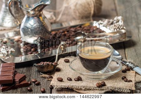 Espresso glass cup with coffee bean, chocolate and creamer on old wooden table