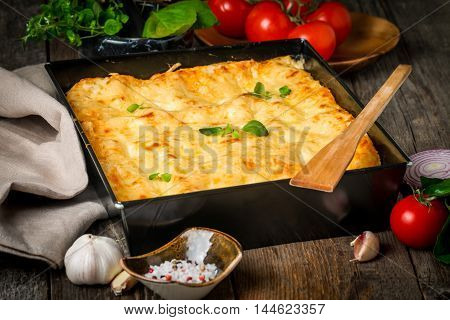 Delicious traditional italian lasagna  with ingredients served on rustic  wooden table