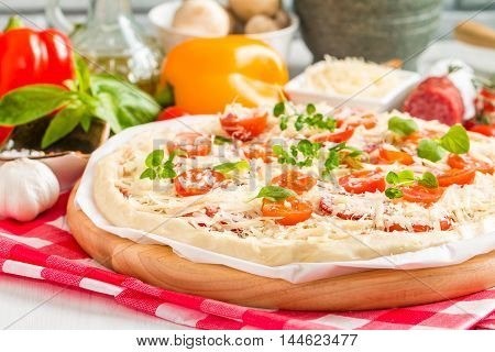 Raw homemade Pizza and Ingredients on white wooden table
