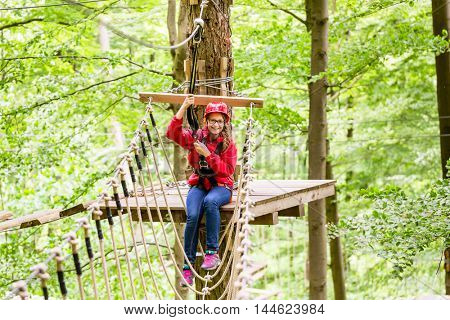 Teenage child enjoying climbing on a high rope course