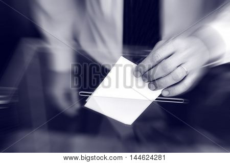 Image of a ballot box and hand putting a blank ballot inside elections voting concept