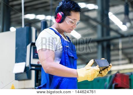 Worker in industrial factory checking work piece in front of metal skip machine