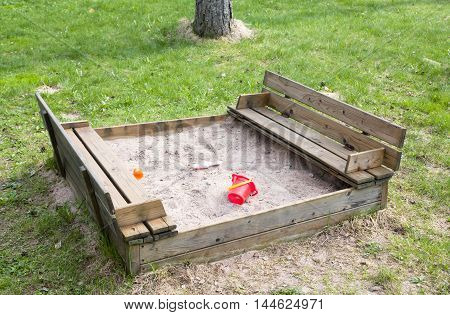 Wooden sandpit in the garden with toys