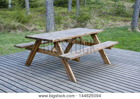 Wooden outdoor furniture on the platform in the garden