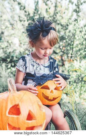 Halloween. Child Dressed In Black With Jack-o-lantern In Hand, Trick Or Treat. Little Girl Looking O