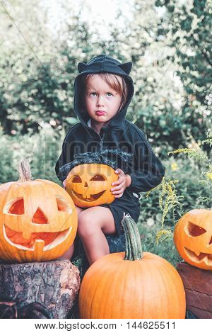 Halloween. Child Dressed In Black With Jack-o-lantern In Hand, Trick Or Treat. Upset Little Girl  Pu
