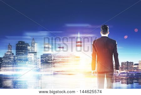 Man in suit standing with back to viewer and looking at big city panorama. Concept of international trade and business companies. Toned image