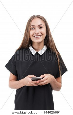 Smiling blond girl in black and white dress with cell phone standing against white background. Isolated. Concept of young teacher