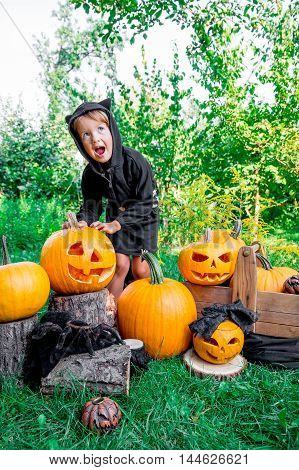 Halloween. Child Dressed In Black With Jack-o-lantern In Hand, Trick Or Treat. Scaring Little Girl