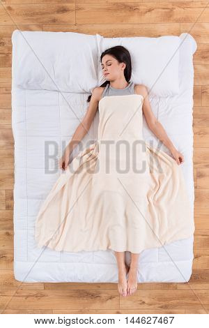 Sleeping lady. Top view of relaxed young woman having pleasant sleep lying in bed under blanket
