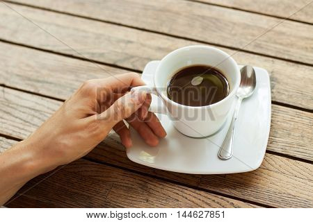 Woman's hand with a white cup of coffee on a saucer with a spoon, standing on a wooden table. The concept of a coffee break, a pleasant time of rest, French cafes, etc.