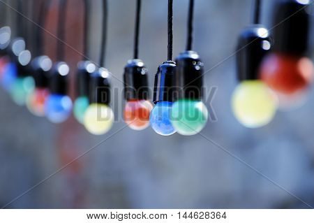 Colored incandescent bulbs hanging on street .