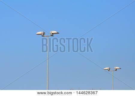 Lamp street lighting on the background of blue sky.