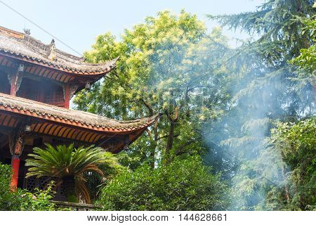 A temple with trees with smoke from burning incense in Chengdu Sichuan Province China
