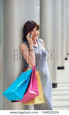 Shopping woman with bags talking on the phone at the mall