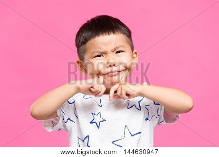 Little kid putting finger on cheek