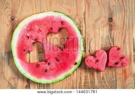 Round watermelon slice with cut in the shape of heart on old wooden background top view