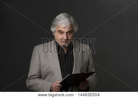 Picture of demanding professor man of university or colleage isolated on black background. Mature teacher posing with clipboard and looking at camera in studio.