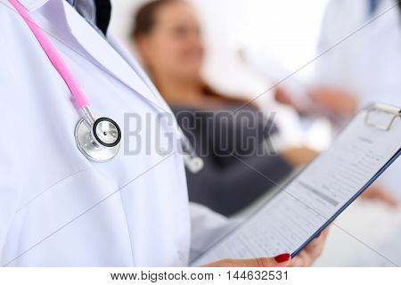 Stethoscope head lying on doctor chest with patient in bed communicating with therapeutist in background. Surgeon or traumatologist physical test 911 prescribe remedy polite personnel concept