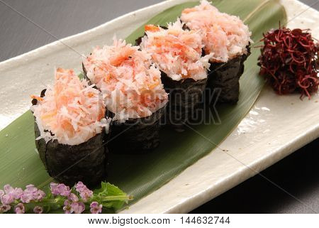 Red snow crab loosened kimbap on green leaf tray in restaurant