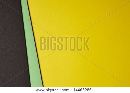 Colored cardboards background in black green yellow tone. Copy space. Horizontal