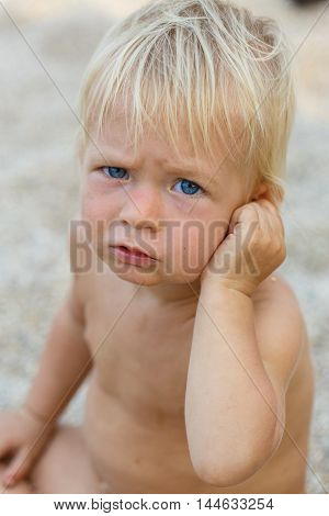 Baby with blond hair is talking on the phone