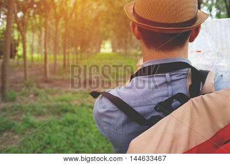 portrait of adventure man with map and extreme explorer gear on forest with sunrise or sunset.
