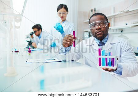 Waist up of male African-American scientist in lab coat and safety goggles looking at camera holding test tubes, female Asian colleague examining flask, male Latin-American scientist in background.