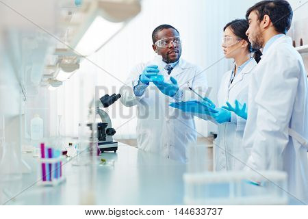 Male African-American laboratory scientist holding flask with blue liquid discussing chemical reaction with male Latin-American and female Asian colleagues.