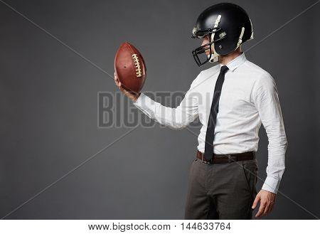 Sideview of businessman in formal clothes and football helmet standing isolated on black background looking in determination at American football.