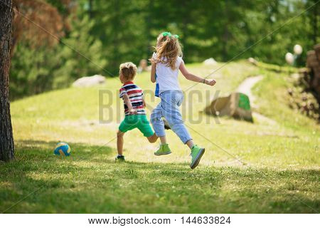 Rear view of blond girl with ponytails and blond boy in striped t-shirt running on green grass towards ball in park on sunny day.