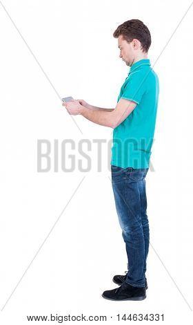 back view of business man uses mobile phone. Curly man in a turquoise jacket stands sideways and playing on the phone.