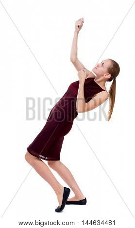 back view of standing girl pulling a rope from the top or cling to something. Isolated over white background. A girl in a burgundy dress pulls the top rope.