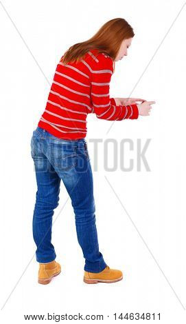 back view of standing young beautiful woman using a mobile phone. blonde in a red striped sweater phone photographing something at the bottom.