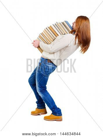 Girl carries a heavy pile of books. back view. Blonde in a white blouse strongly leaned back under the weight of a stack of textbooks.