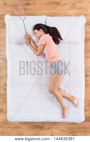 Dreams during sleep. Top view of cheerful young woman holding badminton bird and racket while sleeping on her side on white bed and dreaming about her hobby