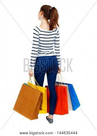 back view of woman with shopping bags. backside view of person. Isolated over white background. Girl in striped sweater holding colorful shopping bags.